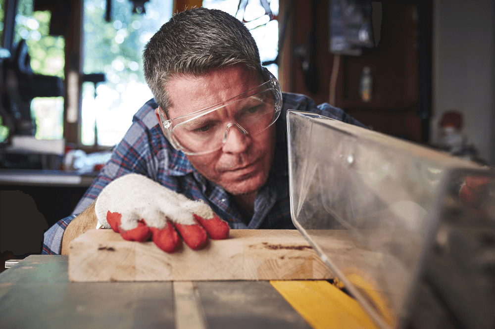 A man Cutting wood on a table saw