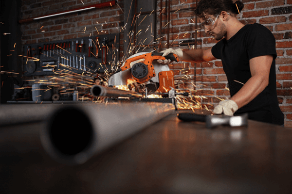 man cutting steel pipe using best miter saw