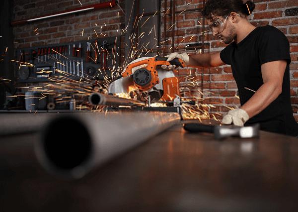 man cutting steel pipe using best miter saw