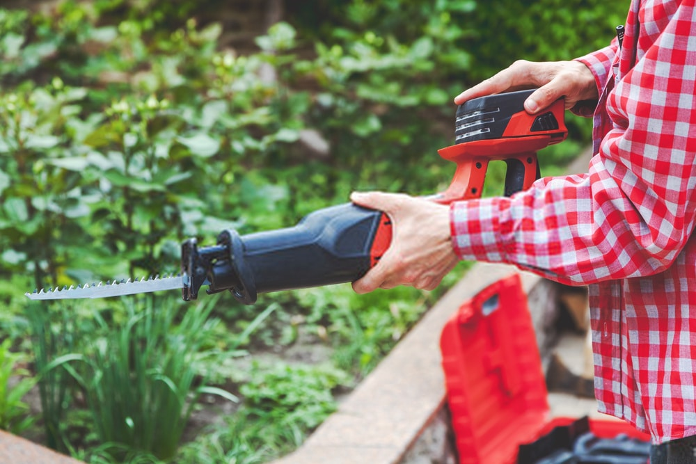 Man Holding a Reciprocating Saw