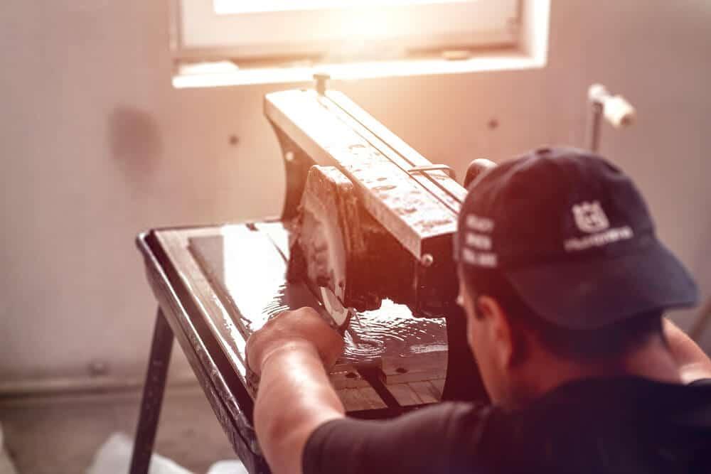 Man cutting tile on wet saw machine