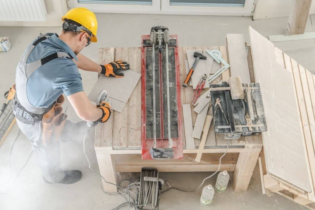 Worker cutting tile on the table