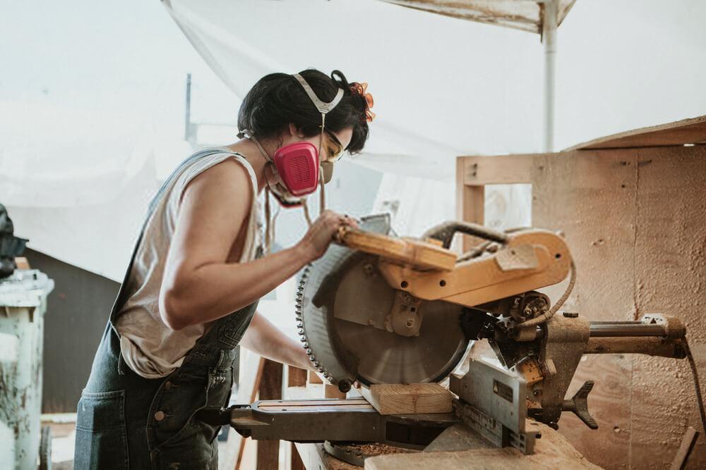 Female carpenter using a compound miter saw