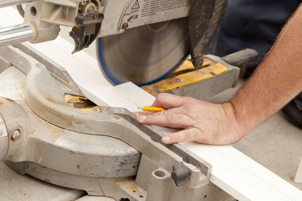 Worker cutting wood using miter saw