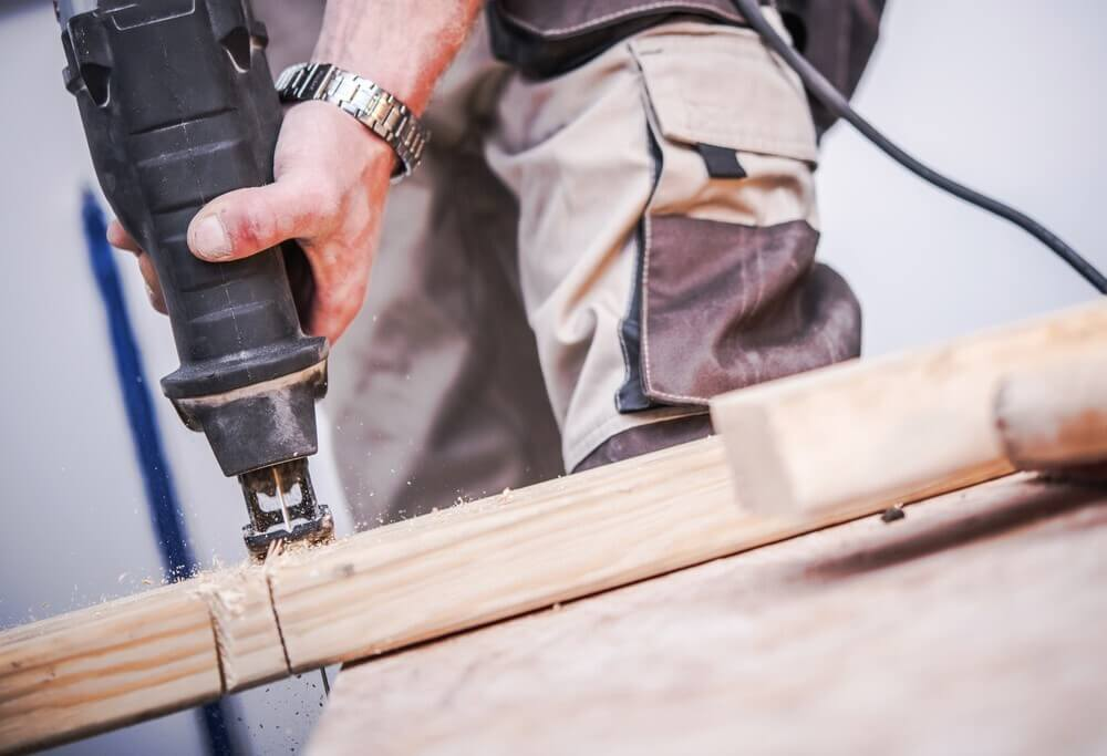 Male carpenter cuts wood with reciprocating saw