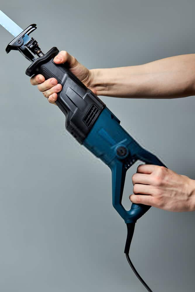 Male hands pressing the trigger of Reciprocating saw