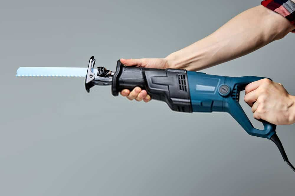 Reciprocating saw with blade in male hands