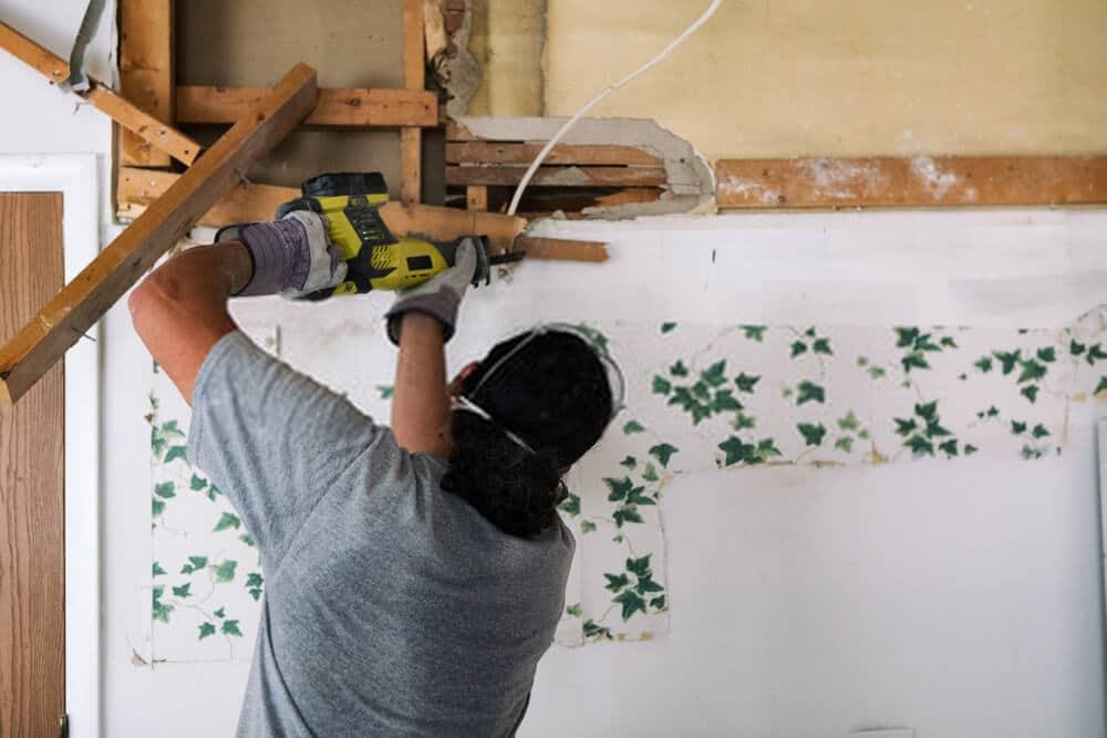Man Uses Reciprocating Saw To Cut Wood Beam