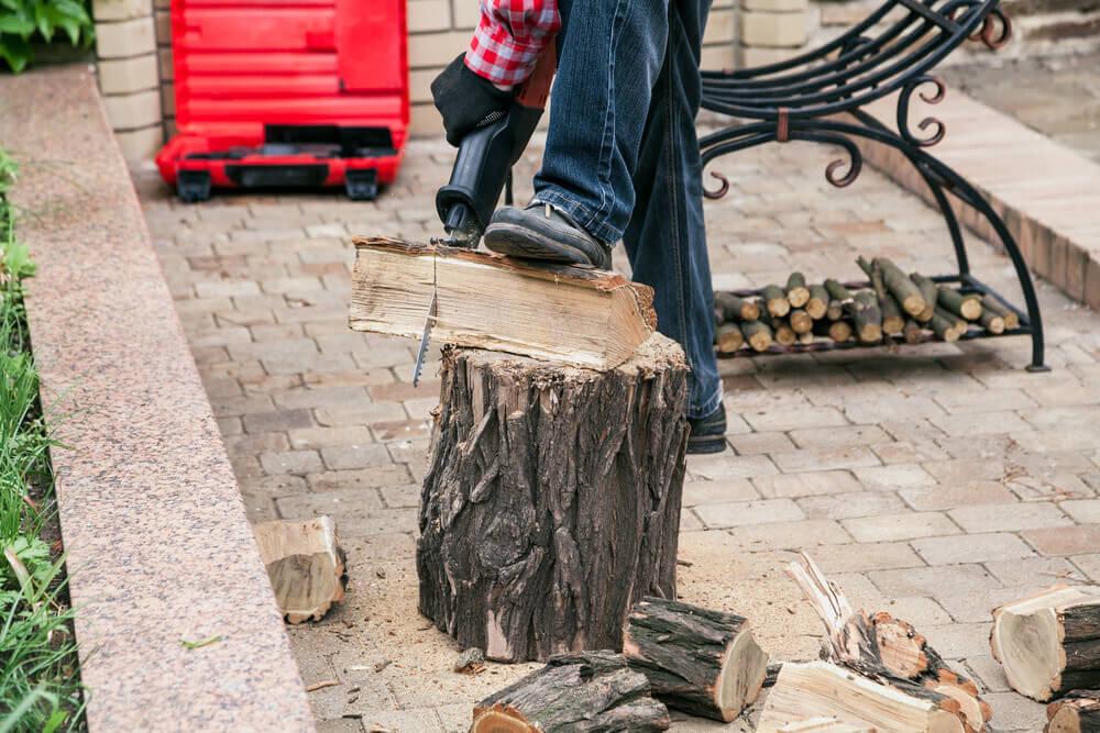 man sawing log on electric Reciprocating saw