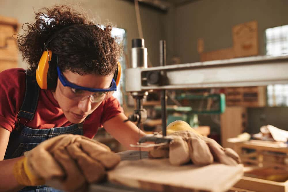 young concentrated female carpenter in safety glasses