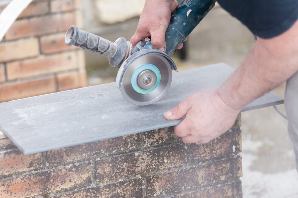 construction worker uses a grinder for cutting a tile