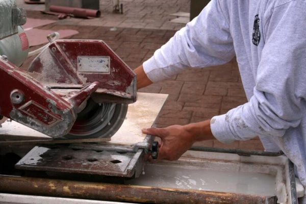 Tiler cutting tile on a tile saw